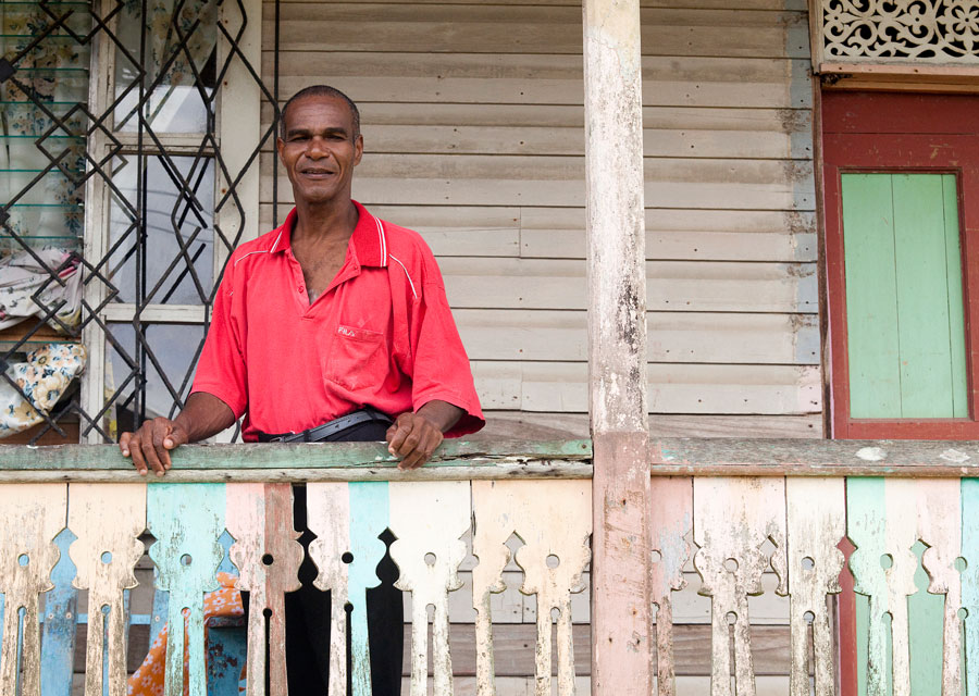 A Cahuita resident on the verandah of his wooden house in the traditional architectural style.